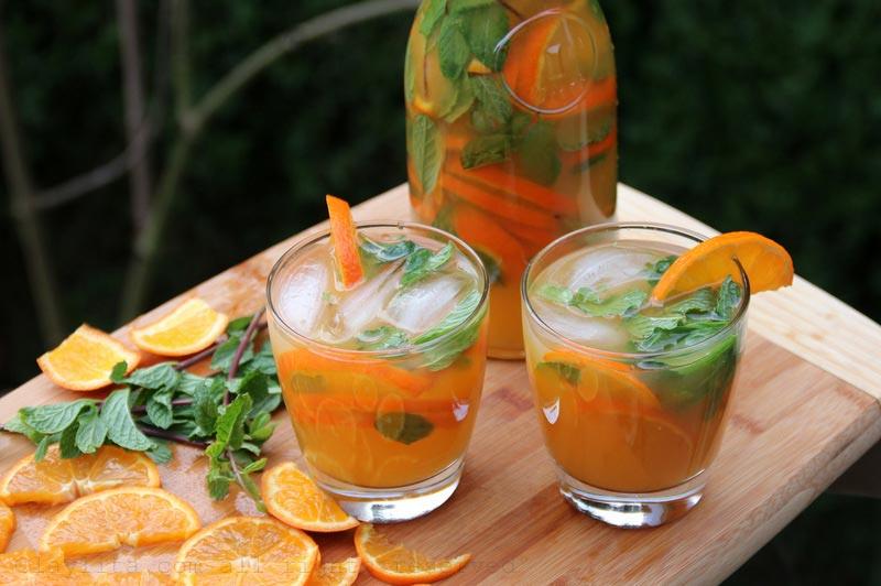 将冰块、薄荷叶和水果片放进个别玻璃杯中并上桌