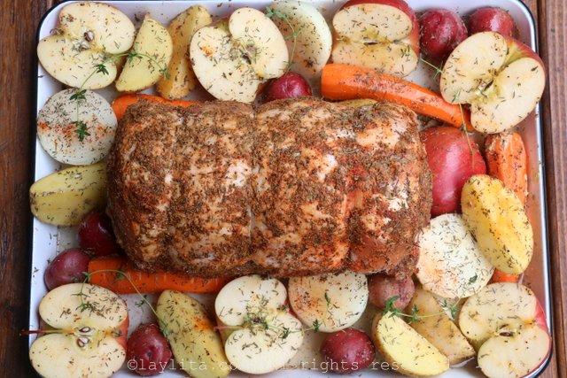 将调味料的混合揉在猪肉上,然后放入带有苹果和蔬菜的烤盘中