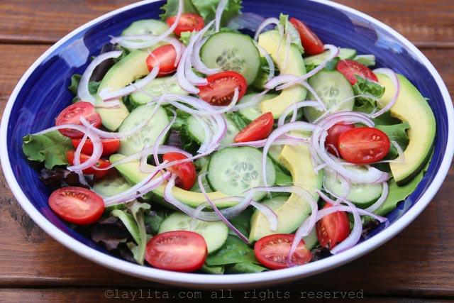 将生菜、牛油果片、洋葱、黄瓜和番茄放入沙拉碗中