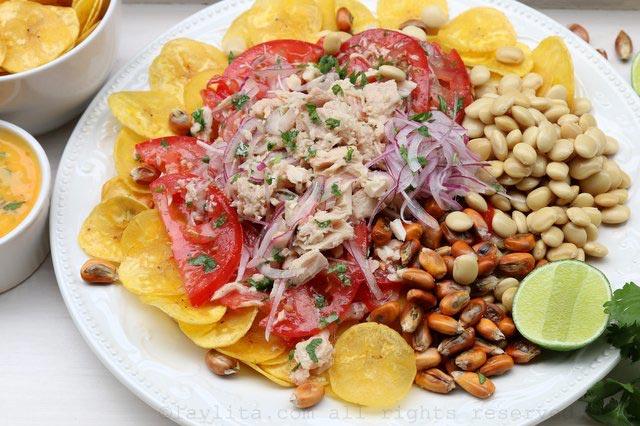将绿色芭蕉片、羽扇豆以及烤玉米坚果放置在大盘上。添上番茄、洋葱和金枪鱼混合