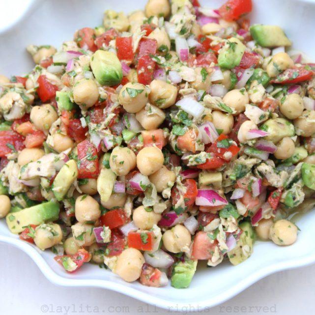 Preparing a chickpea salad with avocado, tuna fish, onions, tomato, and cilantro